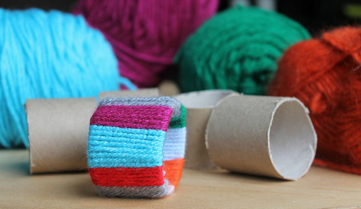 All you need is yarn and empty cardboard tubes for your kids to craft their own festive napkin holders.