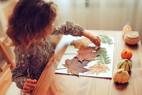Girl pressing fall leaves in scrap book